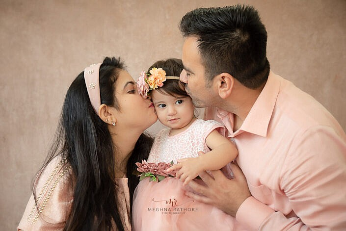 mom and dad kissing girl kid kissing on forehead brown backdrop photo shoot by Meghna Rathore Photography gurgaon