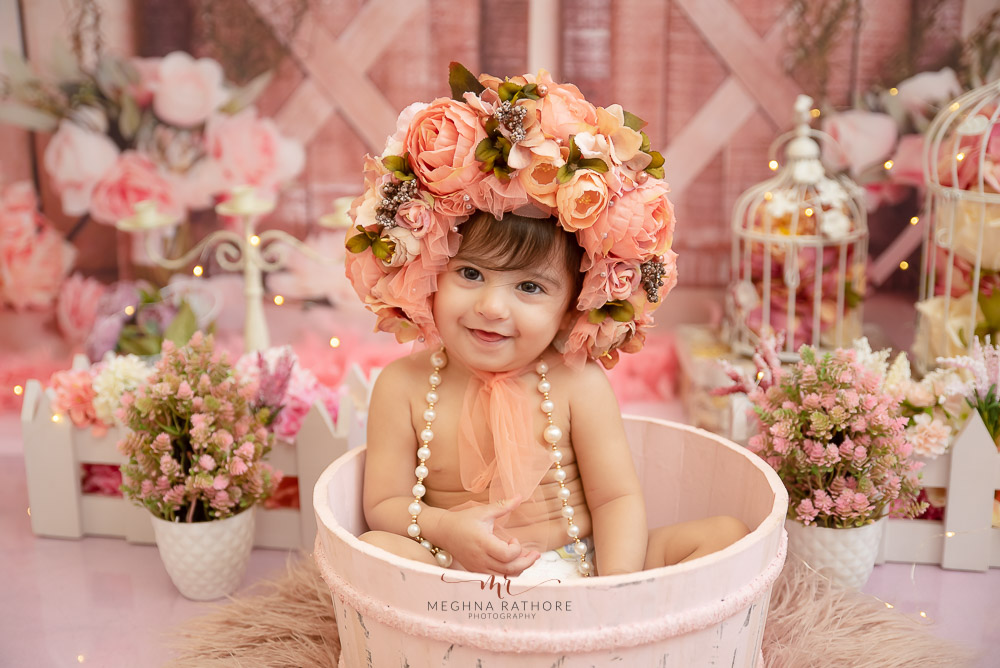 girl kid one year sitting in a wooden tub with pearl necklace flower headband decoration props photo shoot by Meghna Rathore Photography Faridabad