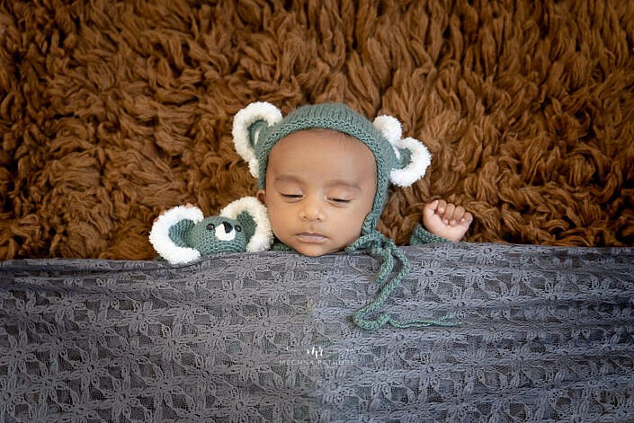 newborn baby lying ona brown fur covered in grey cloth photo shoot by Meghna Rathore Photography