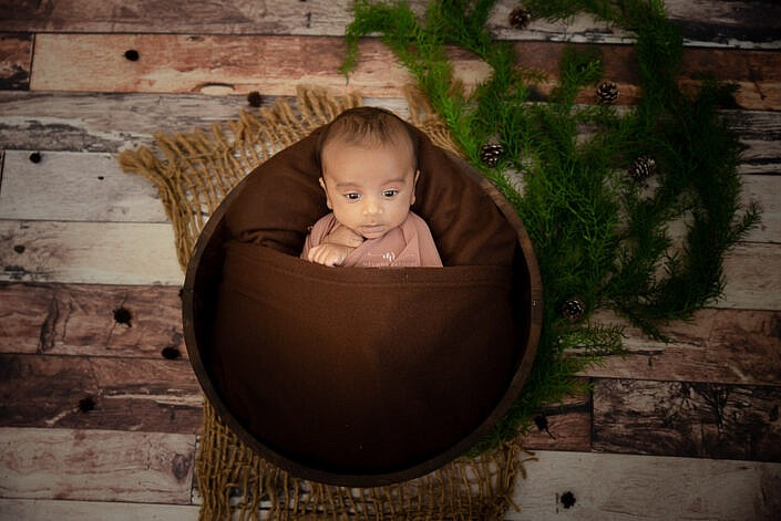 newborn baby lying in a basket with a wood backdrop photo shoot by Meghna Rathore Photography