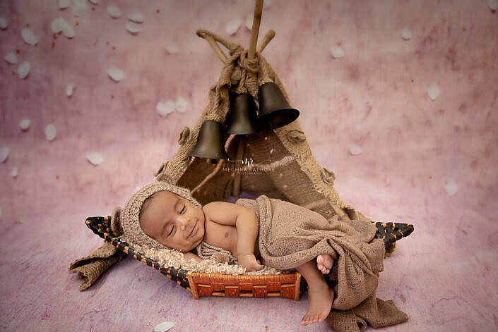 newborn baby lying in a basket shape of boat covered in a brown cloth photo shoot by Meghna Rathore Photography