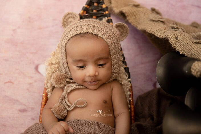 newborn baby with a brown cap lying and smiling photo shoot by Meghna Rathore Photography