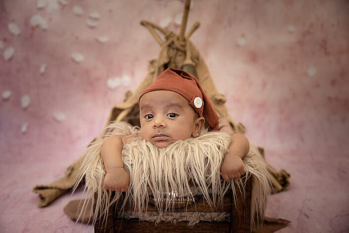 newborn baby lying and looking with cute eyes in a rustic decoration photo shoot by Meghna Rathore Photography