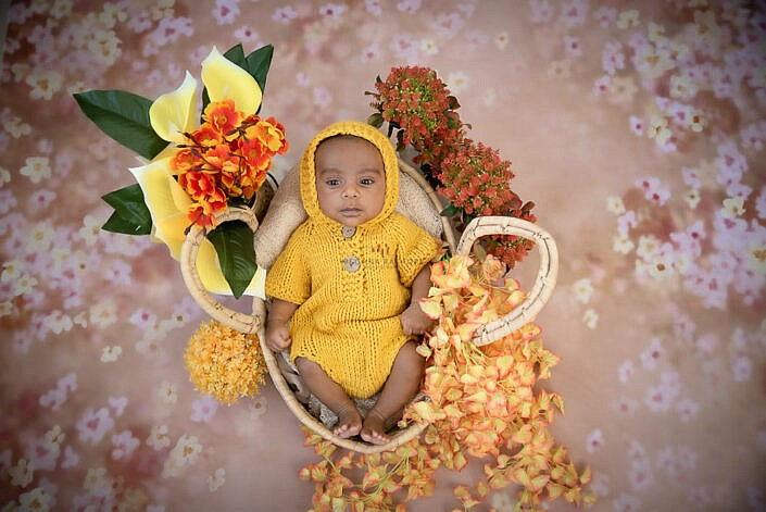 newborn baby wearing yellow knit dress lying in a basket with flower decoration and pink backdrop photo shoot by Meghna Rathore Photography
