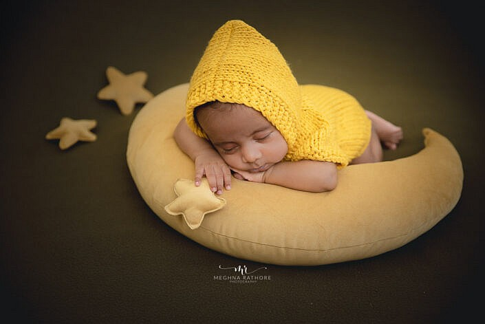 newborn baby in a yellow knit dress lying on a moon prop pillow brown backdrop photo shoot by Meghna Rathore Photography