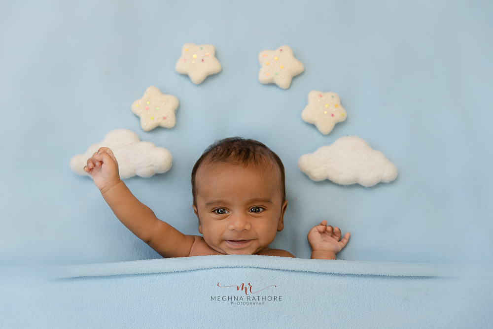 newborn baby on a blue backdrop cloth and cloud and star props photo shoot by Meghna Rathore Photography