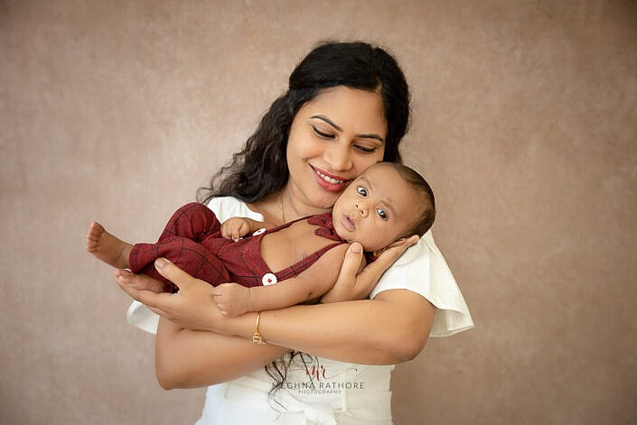 mom holding her newborn in har palm with peach backdrop photo shoot by Meghna Rathore Photography