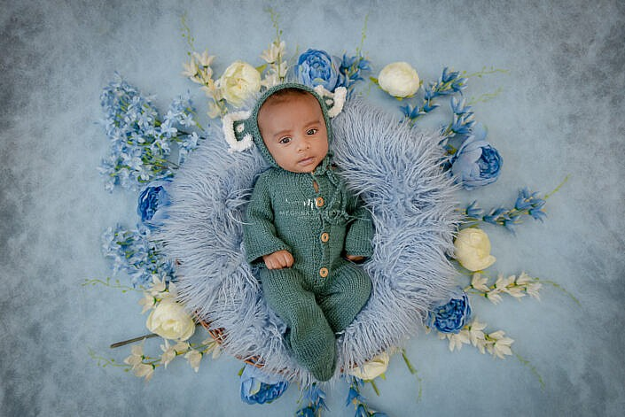 newborn baby in green dress lying on blue fur with a blue backdrop photo shoot by Meghna Rathore Photography