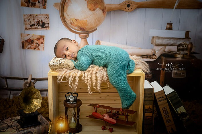 newborn baby in blue dress lying on a wood box photo shoot by Meghna Rathore Photography