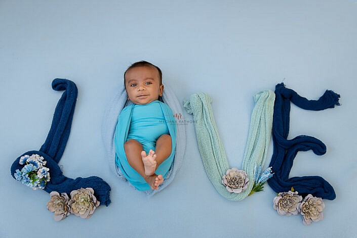 newborn baby in blue dress placed in symbol of love made by cloth photo shoot by Meghna Rathore Photography