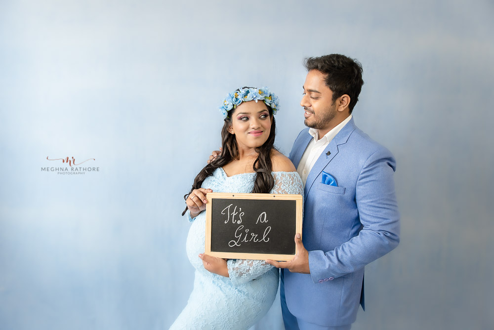 delhi maternity photoshoot by professional maternity photographer Meghna Rathore husband hugging pregnant wife holding chalk board with message