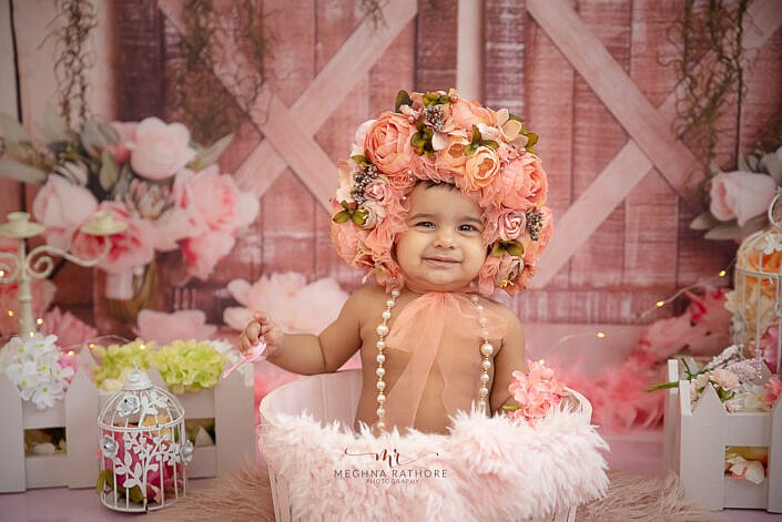 girl kid making facial expression sitting in wooden bowl with pink fur flower headband photo shoot by Meghna Rathore Photography gurgaon