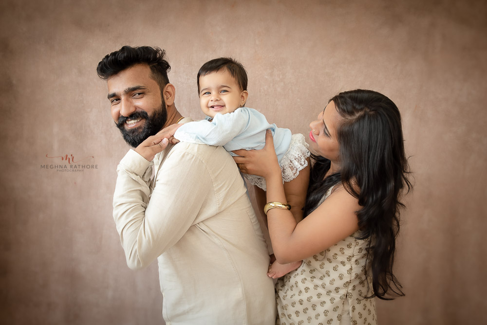baby girl riding father back holded by mom smiling family portrait indoor studio photo shoot by Meghna Rathore Photography Gurgaon