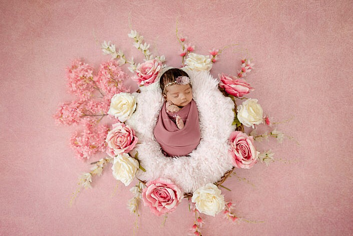 newborn baby lying in a basket with white fur surrounded by flower decoration on a pink backdrop photo shoot by Meghna Rathore Photography