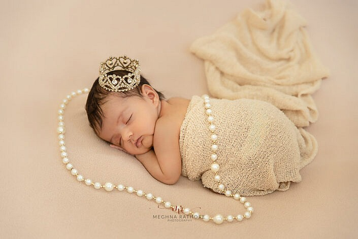 newborn baby wrapped in beige cloth pearl necklace photo shoot Meghna Rathore Photography