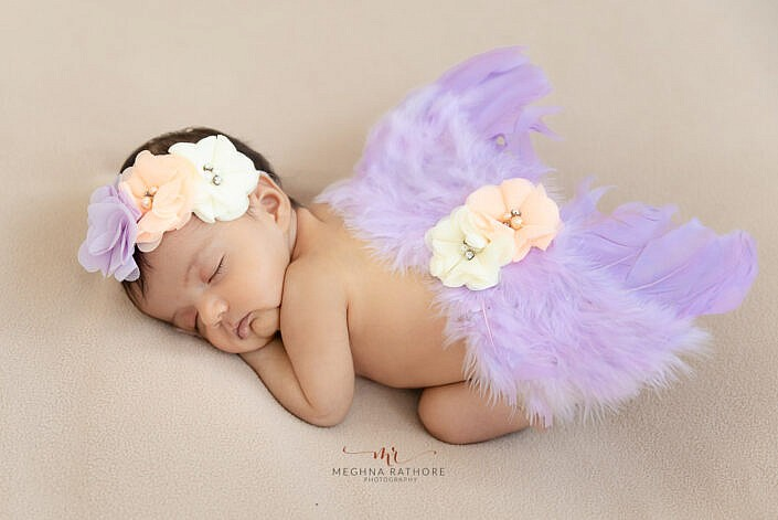 newborn baby with purple angle wings photo shoot Meghna Rathore Photography