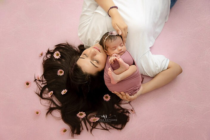 newborn baby wrapped in cloth lying with mom with flowre decoration on pink backdrop photo shoot by Meghna Rathore Photography