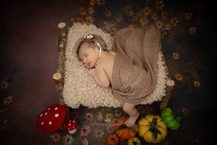 baby on wooden bed brown backdrop newborn photo shoot Meghna Rathore Photography