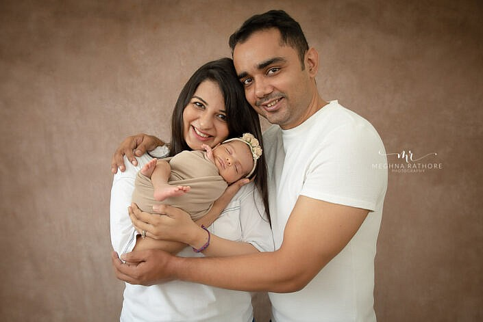mother father holding newborn wrapped in beige wrap Meghna Rathore Photography