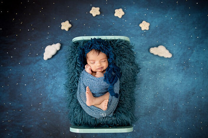 newborn sleeping on a blue bed with blue cover and blue twinkling backdrop with clouds and star props photo shoot by Meghna Rathore Photography