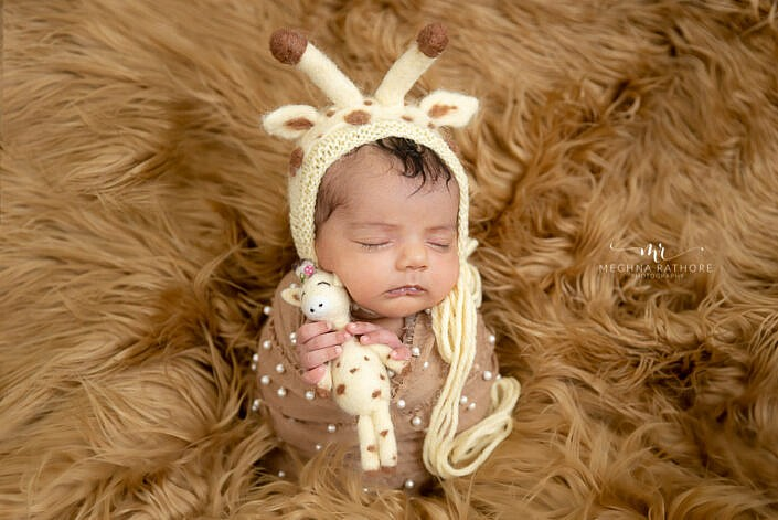 baby in brown fur holding a buddy with bunny cap Meghna Rathore Photography