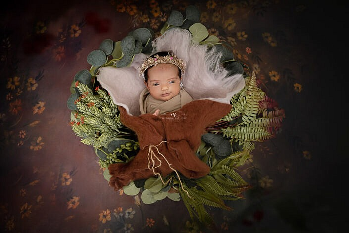 newborn baby lying in a cacon made of cloth with leaves decortion around brown backdrop photo shoot by Meghna Rathore Photography