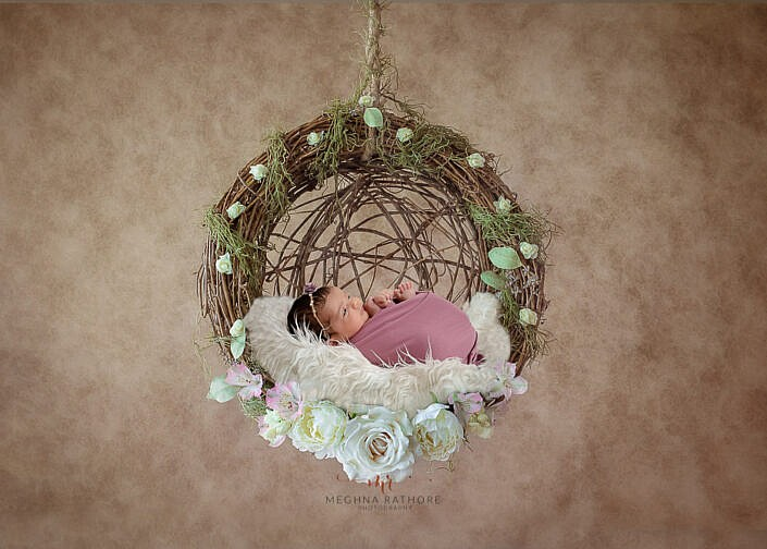newborn baby wrapped and lying in a handing swing made of sticks photo shoot by Meghna Rathore Photography