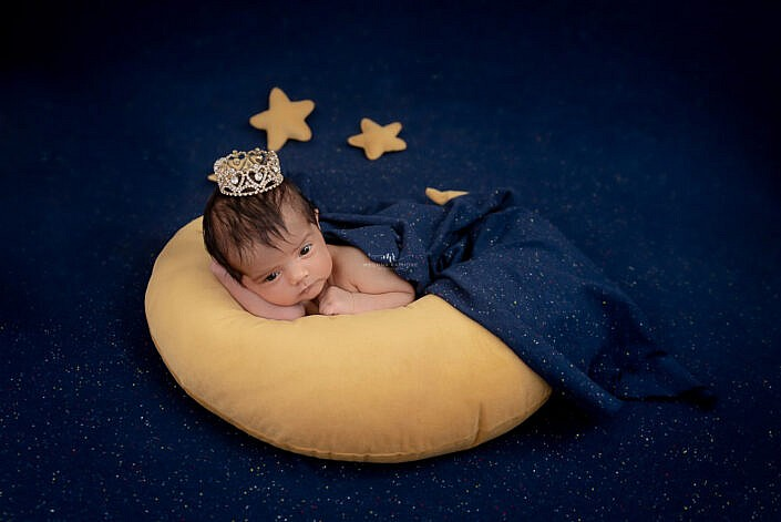 newborn covered in blue cloth lying on a moon prop with small crown at head photo shoot by Meghna Rathore Photography