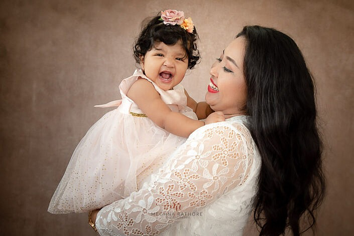 mom wearing white dress holding girl kid smiling and laughing photo shoot by Meghna Rathore Photography delhi