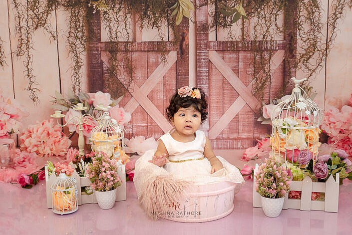 girl kid wearing peach dress sitting in wooden bowl flower decoration pink backdrop photo shoot by Meghna Rathore Photography delhi gurgaon