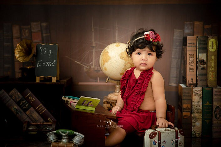 baby kid photoshoot girl wearing red dress with props and study backdrop photo shoot by Meghna Rathore Photography delhi