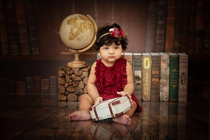 girl kid with red dress with globe and wood cube study backdrop photo shoot by Meghna Rathore Photography Faridabad