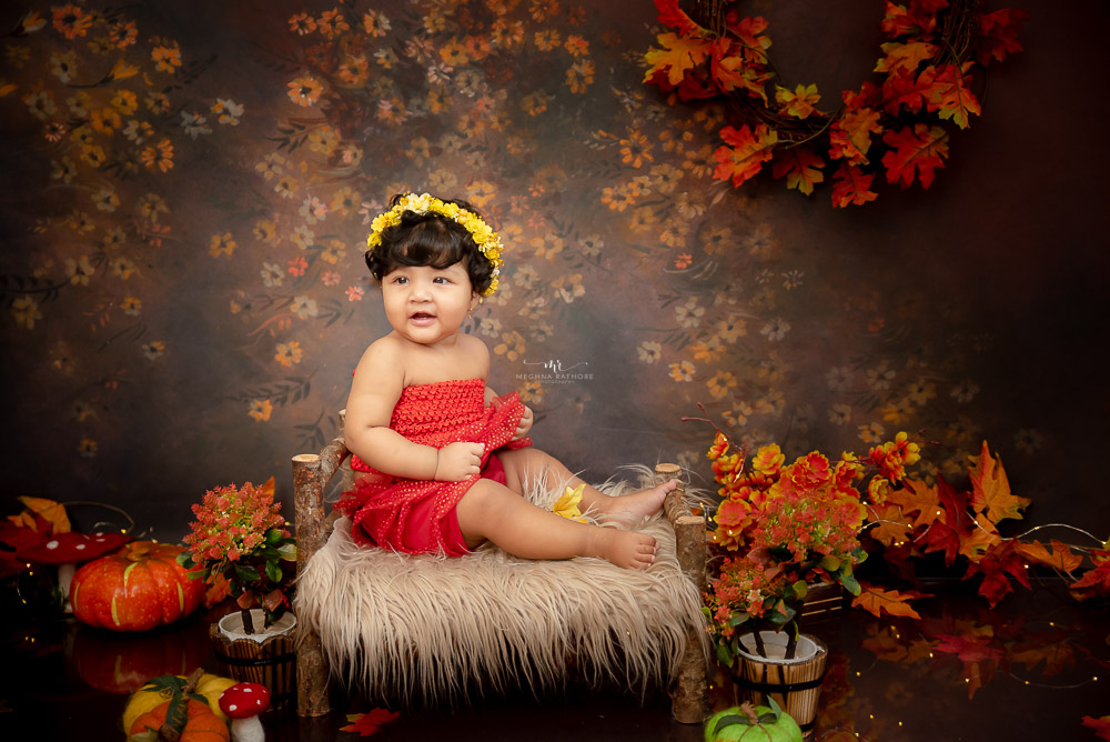 baby kid photoshoot girl sitting on a bed log with spring backdrop