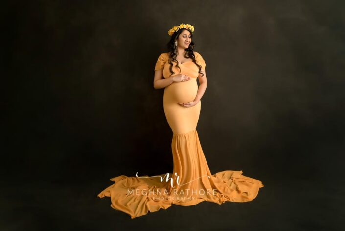 gurgaon maternity portrait photo shoot in home studio mother wearing yellow dress with black backdrop