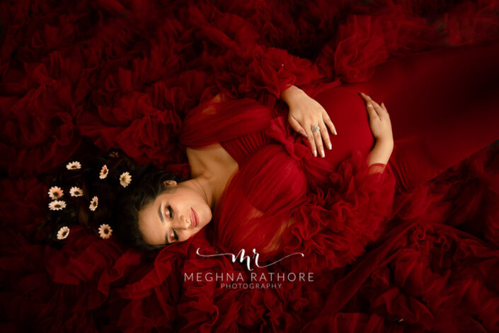 Delhi maternity photographer such an amazing lying floor image of mom to be in maroon gown maternity shoot by Meghna Rathore Photography