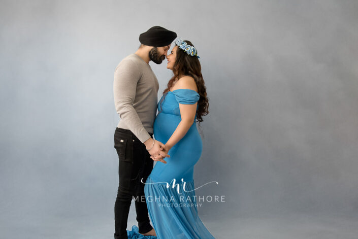 Delhi maternity photographer lady wearing blue gown and posing with husband maternity shoot by Meghna Rathore Photography