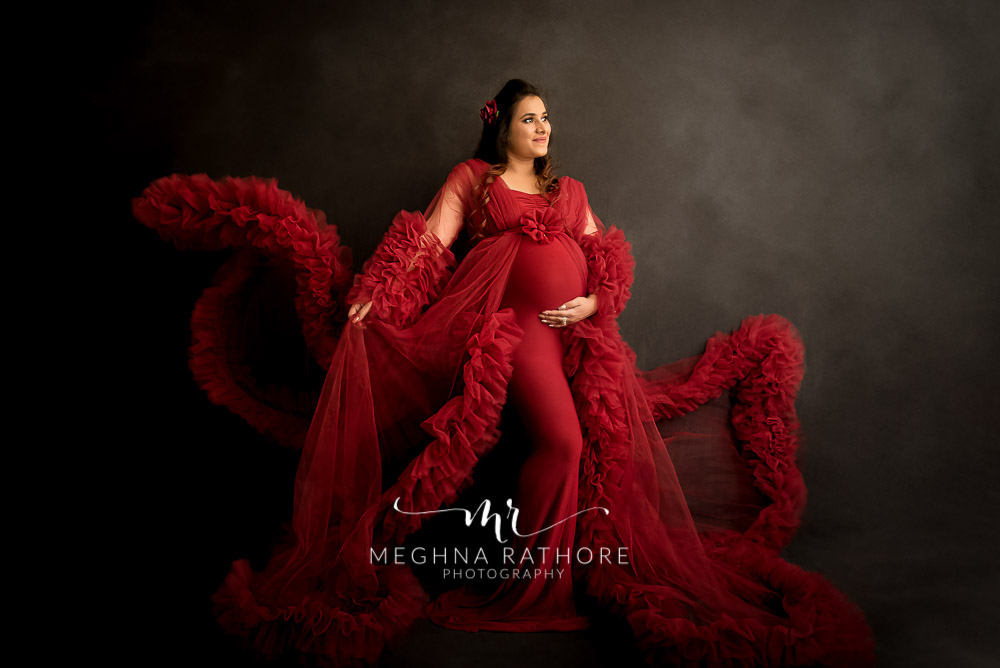 Delhi maternity photographer new mom to be wearing red fluffy dress and posing with flurry dress trail in hand maternity shoot by Meghna Rathore Photography