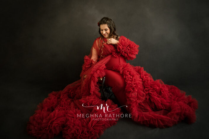 Delhi maternity photographer mom to be wearing red tutu gown and posing on a bench sitting maternity shoot by Meghna Rathore Photography