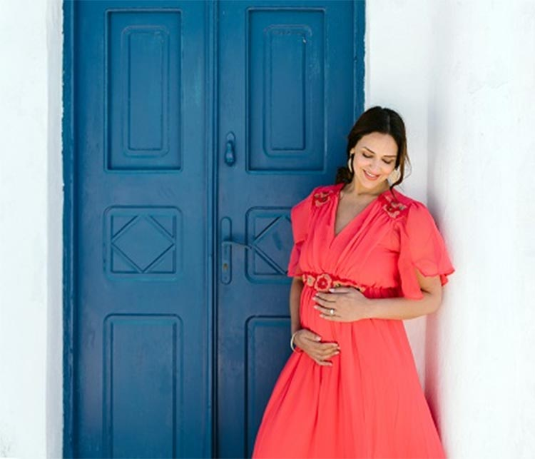 bollywood celebrity esha deol maternity photoshoot in greece wearing red gown against blue door