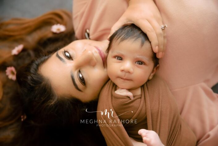 Newborn baby with mother posing together at meghna rathore photography in gurgaon