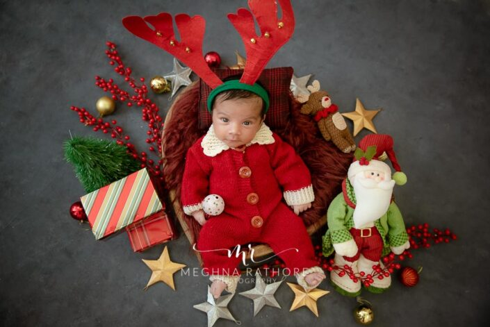 Newborn baby boy posing with christmas themed props around him at meghna rathore photography in gurgaon