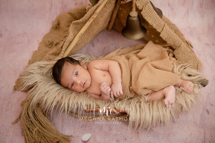 26 days old newborn baby boy posing with different props and theme at meghna rathore photography in gurgaon