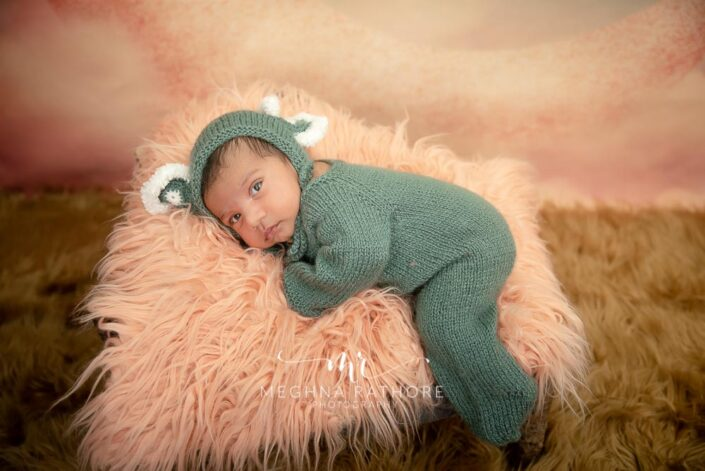 26 days old newborn baby boy posing with some props and a theme at meghna rathore photography in gurgaon