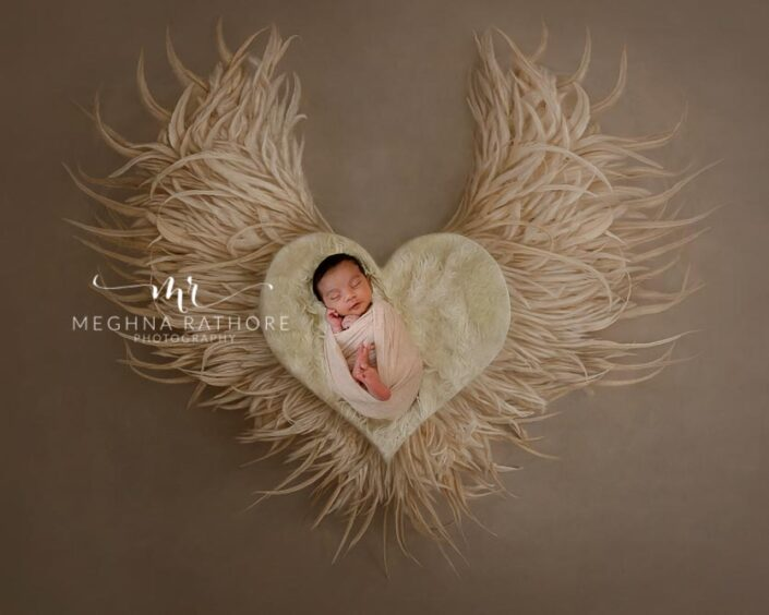 Newborn baby posing with props shaped like heart and wings at meghna rathore photography in delhi gurgaon