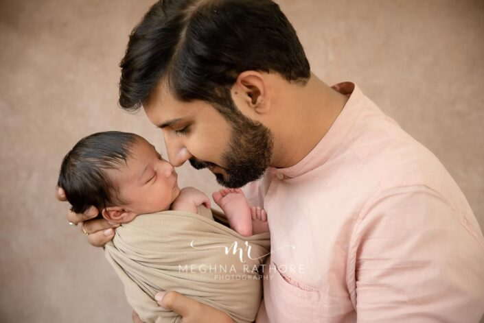 26 days old newborn baby boy posing with father at meghna rathore photography in gurgaon