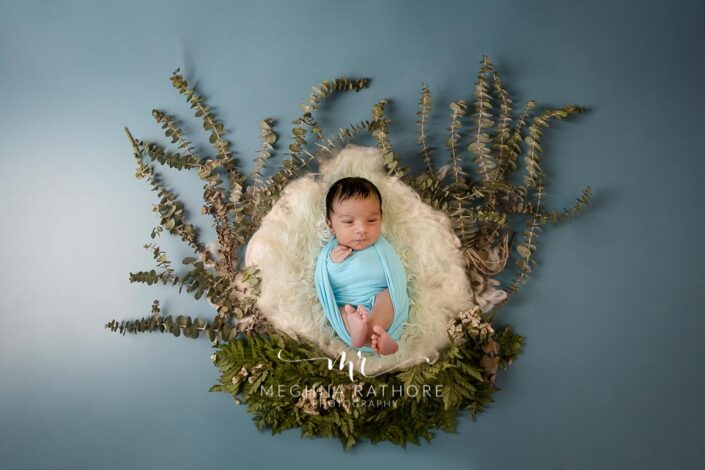newborn baby boy posing with props such as leaves surrounded by him at meghna rathore photography in delhi