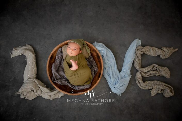 26 days old newborn baby boy tucked in basket and posing along with different cloth props at meghna rathore photography in delhi