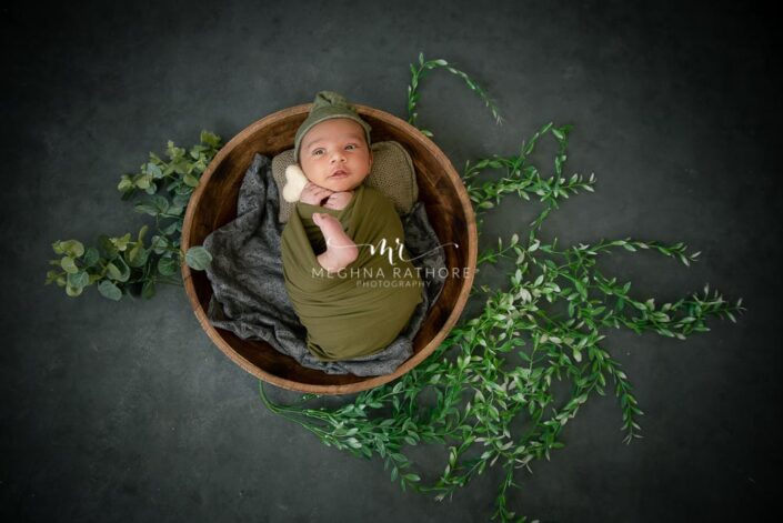 Newborn baby boy in green and grey colored theme and props at meghna rathore photography in delhi