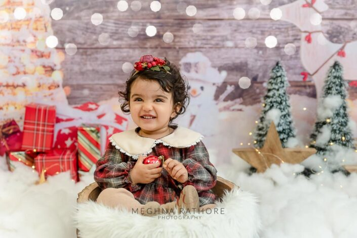 1 year old girl posing smiling in a christmas themed professional photoshoot at meghna rathore photography in delhi gurgaon