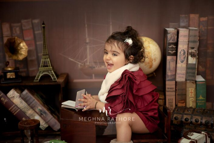 1 year old baby girl posing in red colored outfit with theme and props at meghna rathore photography in delhi gurgaon
